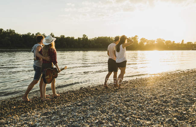 Two couples walking at the riverside at sunset — Stock Photo