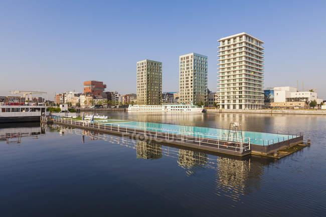 Belgium, Flanders, Antwerp, former dock area, swimming swimming pool, apartment buildings against water — Stock Photo