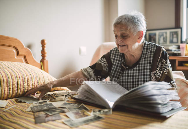 Senior woman looking old photos of childhood at home — Stock Photo
