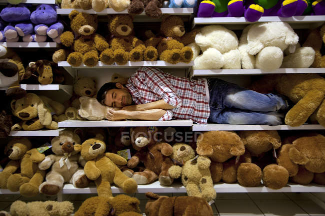 Man sleeping on a shelf between soft toys in a supermarket — Stock Photo