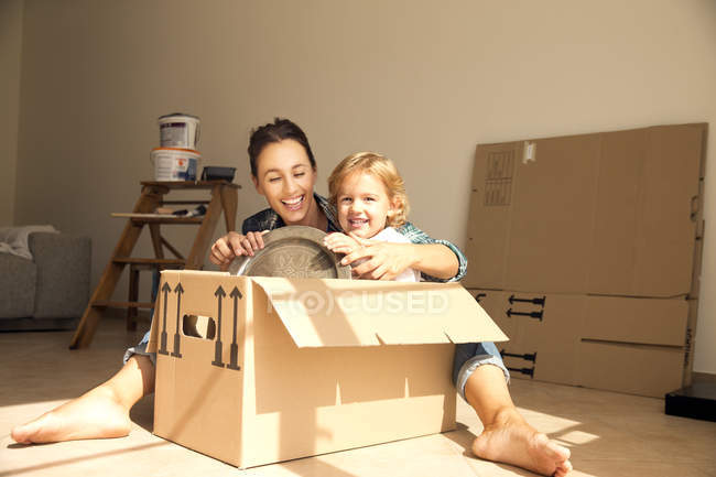 Happy woman with daughter sitting in cardboard box — Stock Photo