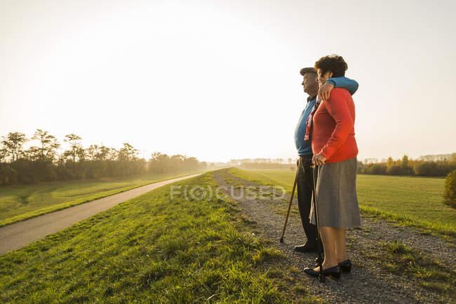 Coppia anziana con bastoni da passeggio in piedi nella natura — Foto stock