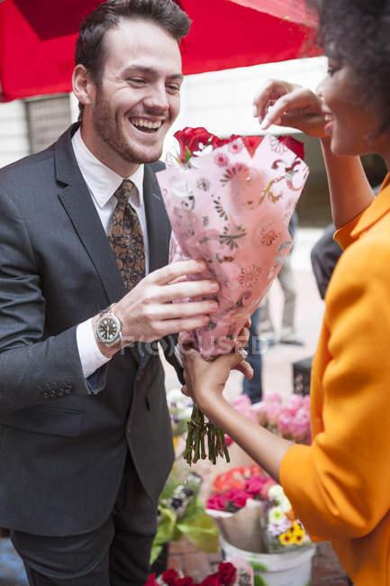 Мужчина покупает красные розы для женщины — стоковое фото