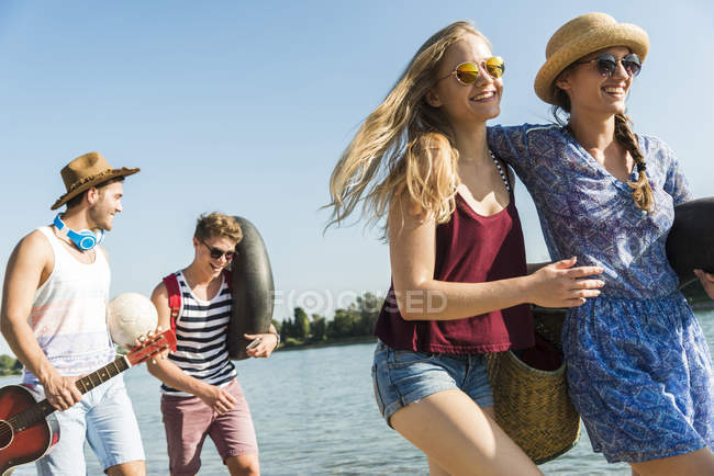 Friends walking with ball and guitar at the riverside — Stock Photo
