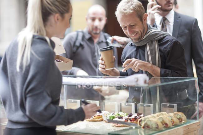 Человек, закупка продуктов питания на рынке города — стоковое фото