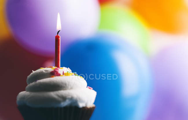 Birthday cup cake with lighted candle in front of balloons — Stock Photo