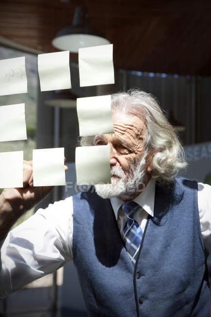 Старший професор писати на клей нотатки — стокове фото
