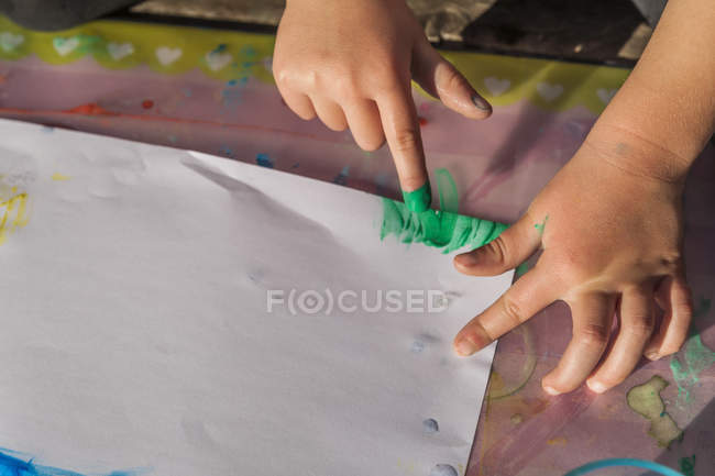 Close-up of Girl painting with finger colors — Stock Photo