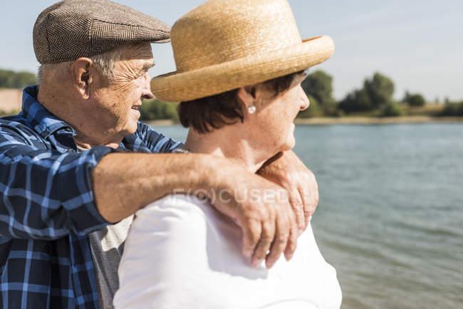 Senior couple relaxing at riverside — Stock Photo