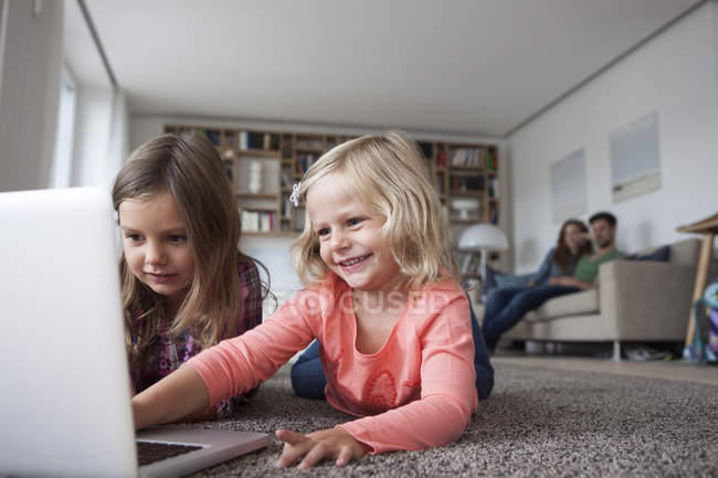 Two little sisters lying on the floor at living room with laptop while her parents sitting in the background — Stock Photo