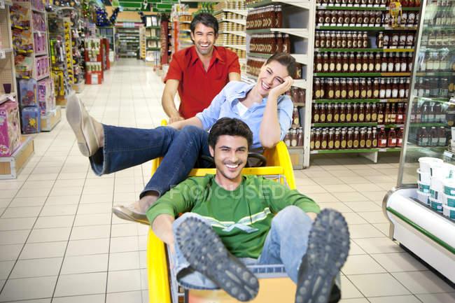 Tre amici che hanno divertimento insieme in un supermercato — Foto stock
