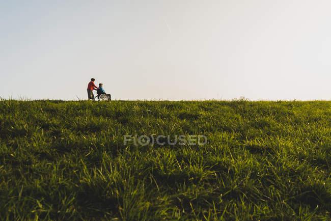 Старшие женщины толкания мужа в коляске в природе — стоковое фото