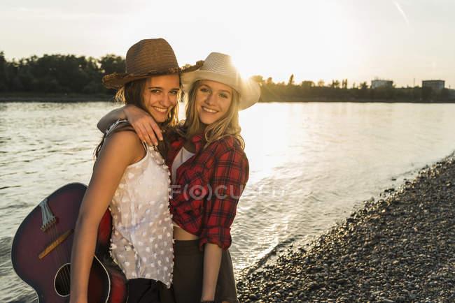 Dos amigos abrazándose en la orilla del río al atardecer - foto de stock