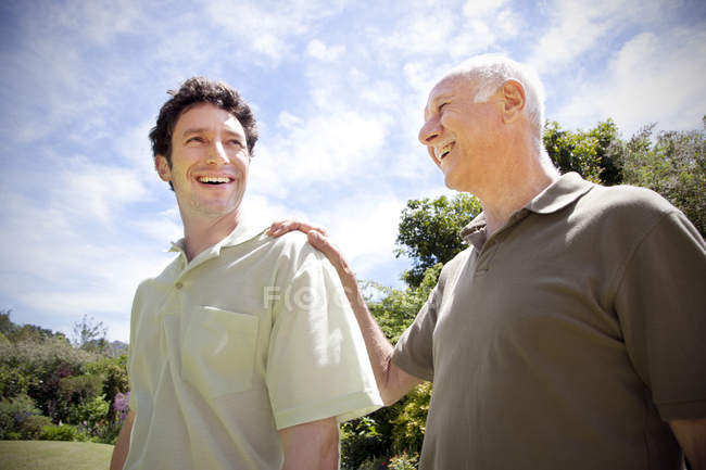 Senior man with his adult son in the garden — Stock Photo