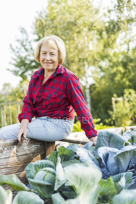 Smiling senior woman at vegetable patch — Stock Photo