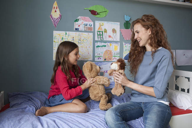 Mother and little daughter sitting on bed in children's room playing together with soft toys — Stock Photo