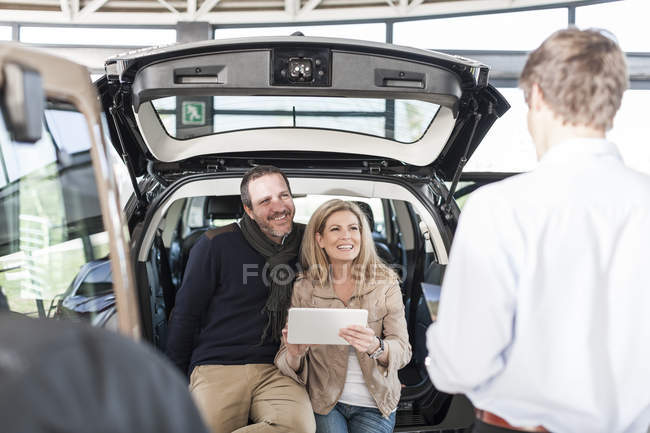 Smiling couple sitting in boot of new car at car dealership — Stock Photo