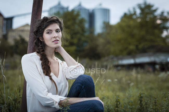 Portrait of woman with braid leaning against pole on meadow — Stock Photo