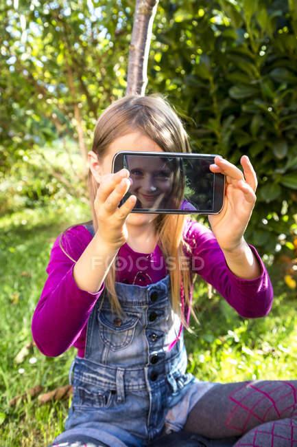 Kleines Mädchen sitzen auf Rasen und Display des Smartphones mit Selfie zeigen — Stockfoto