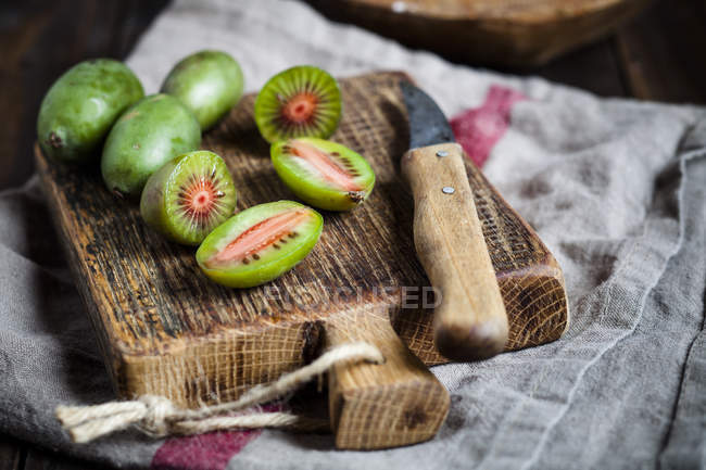 Sliced and whole mini kiwis and kitchen knife on wooden chopping board — Stock Photo