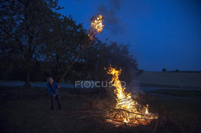 Junge am Lagerfeuer auf einer Wiese am Abend — Stockfoto