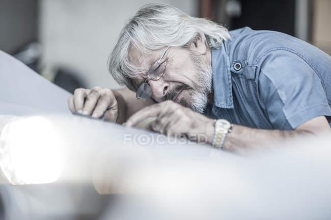 Senior man scrutinizing car — Stock Photo