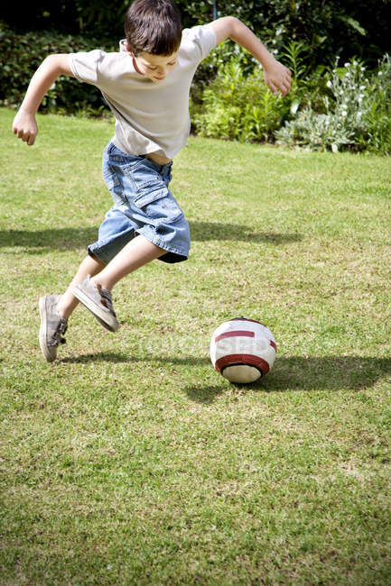 Little boy playing soccer in the garden — Stock Photo