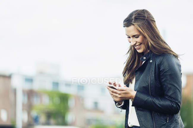 Happy young woman looking at her smartphone — Stock Photo