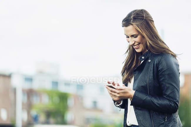 Felice giovane donna guardando il suo smartphone — Foto stock