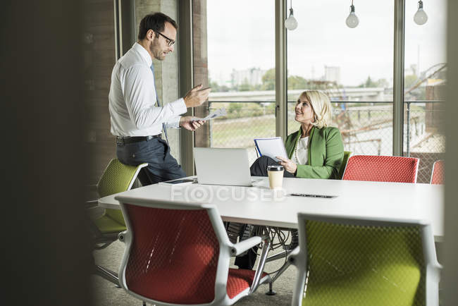 Businessman explaning his colleague something in an office — Stock Photo