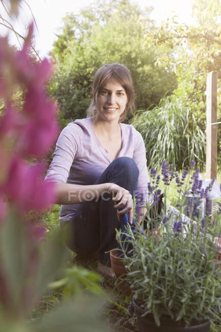 Caucasian smiling woman gardening in flowerbed — Stock Photo