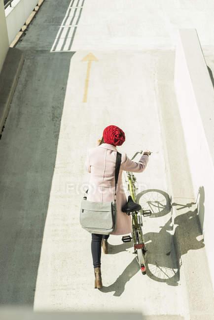 Молодая женщина, нажав велосипедов парковка уровень — стоковое фото