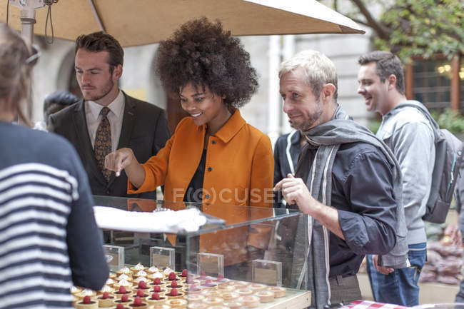 Woman choosing pastries at food stall at city market — Stock Photo