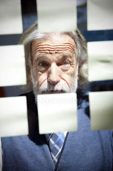 Homem de negócios sênior olhando notas adesivas — Fotografia de Stock