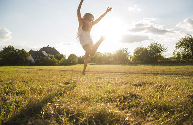 Back view of woman jumping in the air on a meadow at backlight — Stock Photo