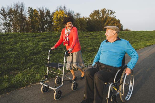 Улыбаясь старший пара с инвалидной коляски и колесных Уокер на пути — стоковое фото