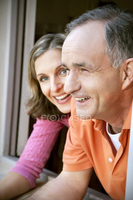 Primo piano dell'uomo e della giovane donna che si appoggia dalla finestra — Foto stock