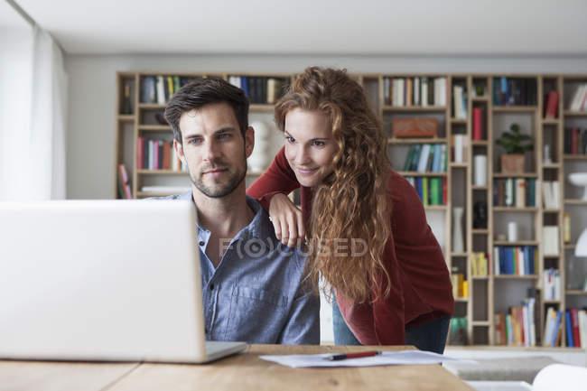 Coppia a casa guardando il computer portatile — Foto stock