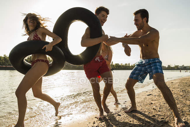 Playful friends with inner tubes having fun on beach — Stock Photo
