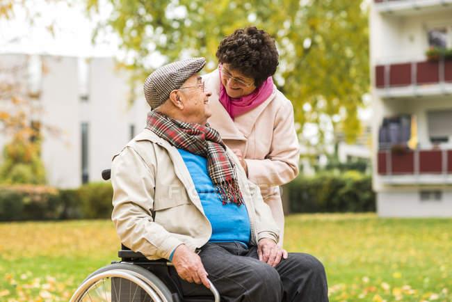Старшая женщина смотрит на мужа в инвалидной коляске — стоковое фото