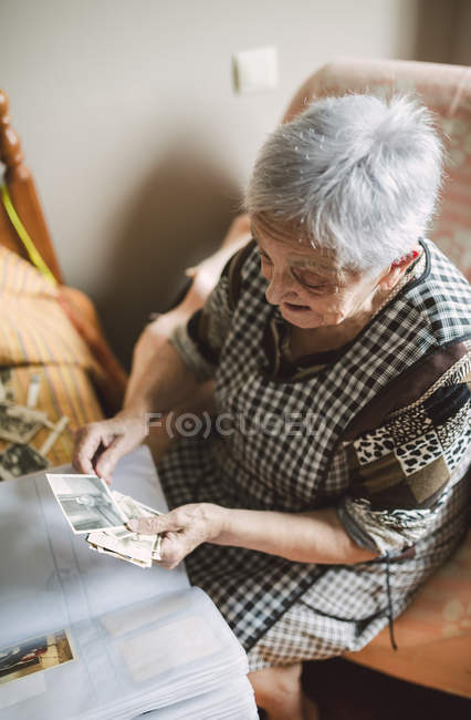Senior woman looking at old photos of her childhood — Stock Photo