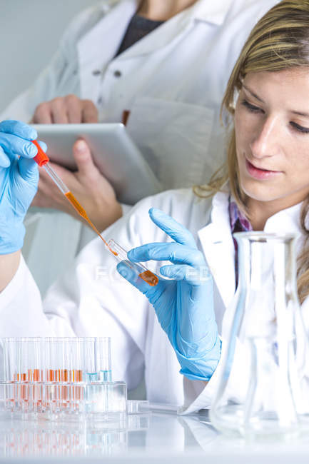 Young female scientist working in lab with pipettes — Stock Photo