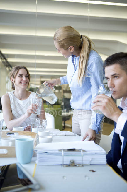 Young Businesswoman pouring water into glass of colleague — Stock Photo