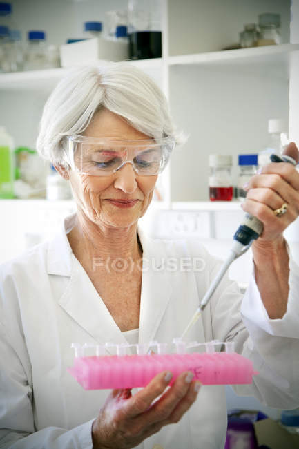 Female professor filling sample glasses in laboratory — Stock Photo