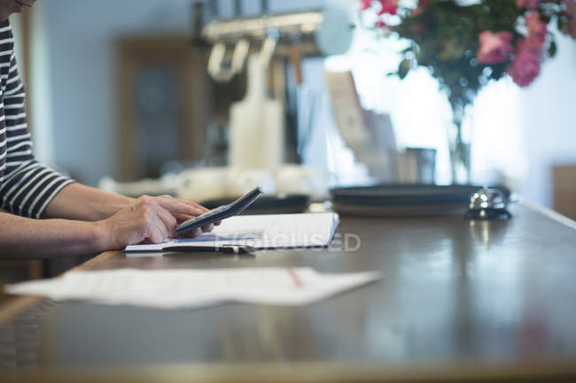 Person at hotel recepetion calculating with calculator — Stock Photo