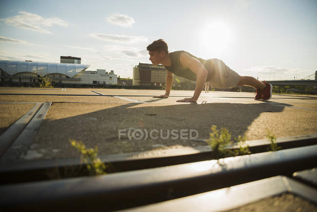 Young man doing push-ups outdoors — color image, one person