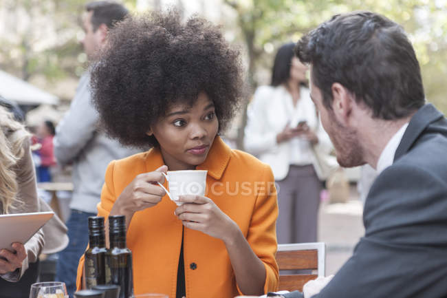 Two colleagues talking and drinking coffee at outdoor cafe — Stock Photo