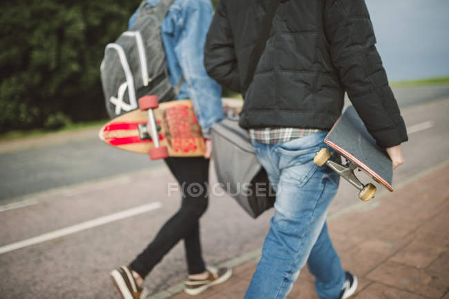 Two walking skaters with longboard and skateboard — Stock Photo
