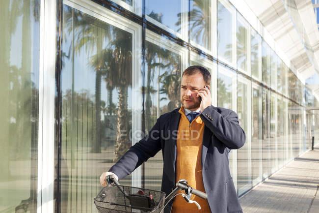 Портрет бизнесмена с велосипедным телефоном со смартфоном — стоковое фото