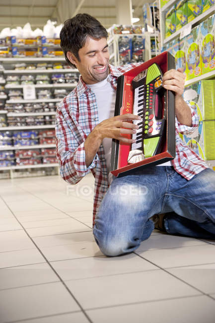 Portrait of happy man crouching on the floor of a supermarket playing with toy keyboard — Stock Photo